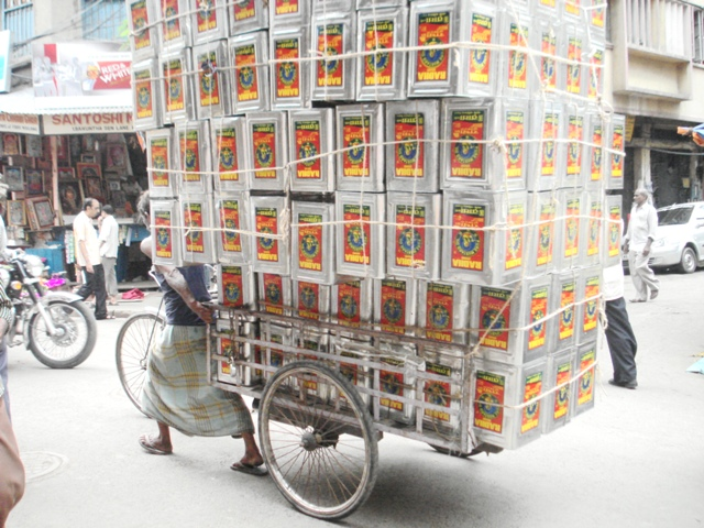 Another hand-pulled rickshaw with tons of oil tins!